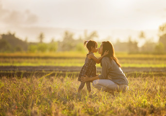 mother and daughter kissing in the field