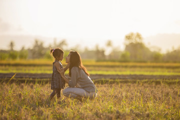 mom and daughter in beautiful sunset scenery