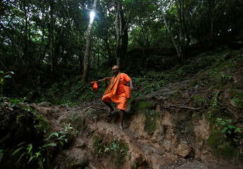 """A devotee chanting the name of Shiva walks along the woods of Sundarijal as he arrives to take a holy dip and fetch water, which is considered holy, from the Bagmati River during the """"Bol Bom"""" (Say Shiva) pilgrimage in Kathmandu"""