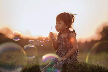 little asian girl playing with soap bubble