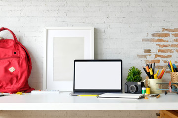 Creative photographer workspace with blank screen laptop on white desk.