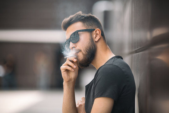 A young handsome white bearded man in black t-shirt smokes a cigarette in the street in the spring. Close up.
