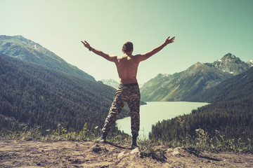 Man jumping Flying levitation with lake and mountains on background Lifestyle Travel happy emotions concept outdoor. Tourist spreading his hands to the side looking at beautiful mountain landscape