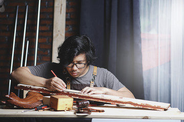 Asian Carpenter Working in Woodworking Workshop. Making Line with Ruler and Pencil on Planks of Wood