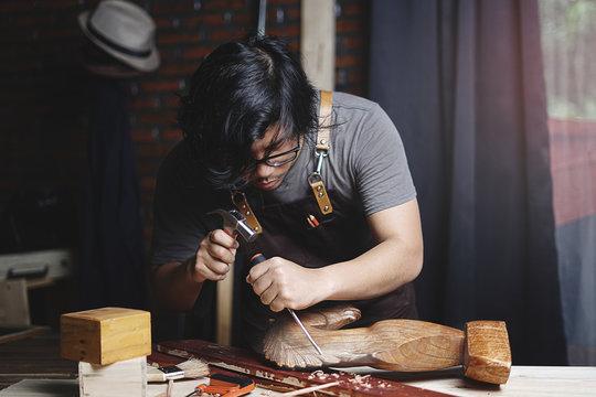 Asian Carpenter Working in Woodworking Workshop. Carving Wooden Horse Sculpture