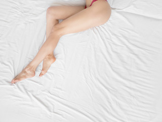 Sexy young naked female legs is lying on white bed covered by blanket