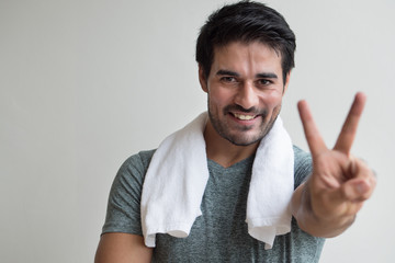 confident fitness man pointing up two fingers; portrait of happy, healthy, confident fitness asian man pointing number two fingers sign, v for victory hand gesture; asian north indian adult man model