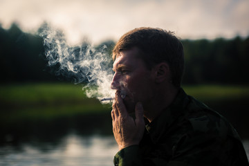 Man Smoking close-up, camouflage clothing, outdoor. Thick smoke and contour light.