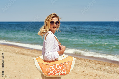 29e5344b09 Portrait of a young woman wearing sunglasses on the beach