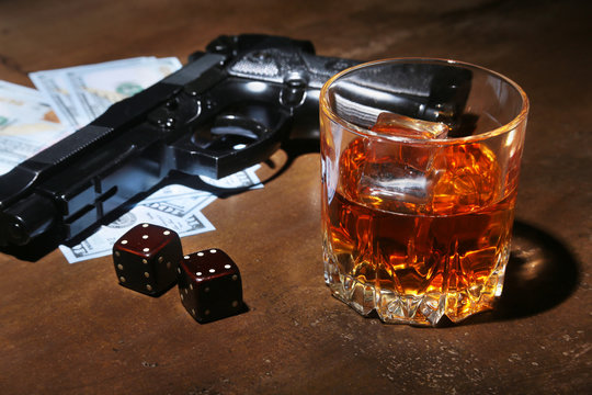 Glass of whiskey or cognac, gun, playing cards with money on the black mirror table. The concept of criminal.
