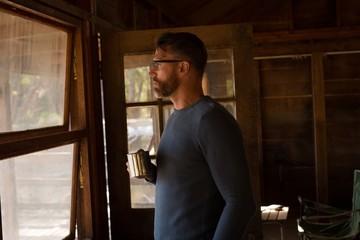 Man with coffee mug looking through window