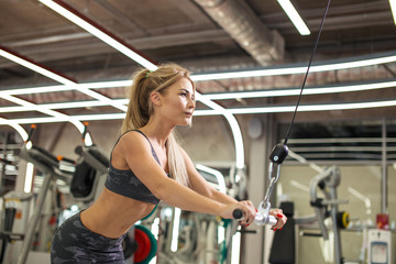 ambitious blond woman working out on the rowing machine. close up side view photo. health care. copy space