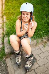 Beautiful curly woman sitting in car park with her inline roller skate and helmet for safety sport