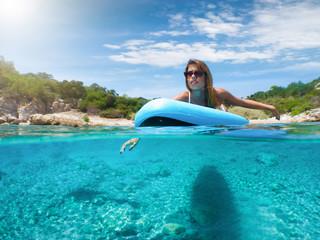 Blonde, sportliche Frau paddelt auf einem Surfbrett über türkises Wasser; unterwasser split Aufnahme