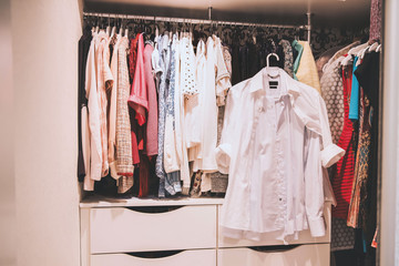 Woman many clothes. Colorful clothes hanging in wardrobe. White men's shirt in women's wardrobe.