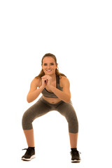 Beautiful young fit woman makes squats isolated over white background