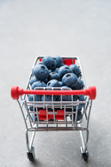 Blueberry fruits in mini shopping cart. Selective focus on the blueberries in small trolley. Copyspace for text.