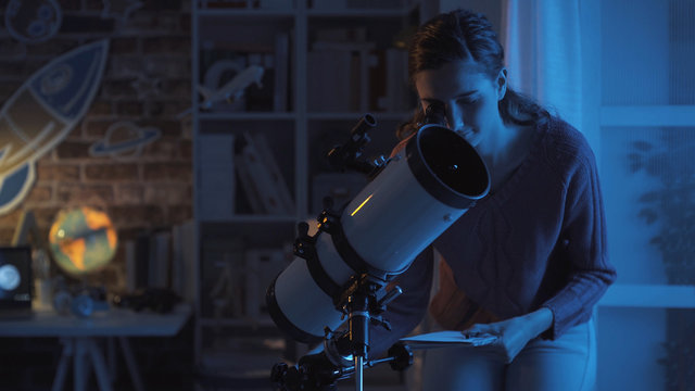Woman stargazing with a professional telescope
