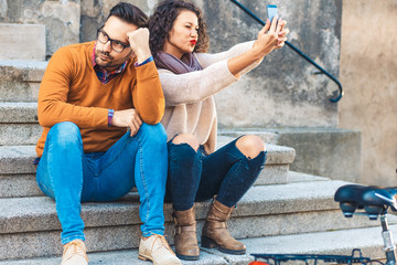 Young couple using mobile phone while sitting on the stairs.