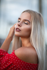 Closeup portrait of sensual blonde model with long blonde hair, posing with closed eyes