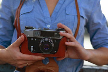 Beautiful hipster girl photographer in blue shirt holding vintage film camera in brown leather case