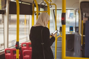 Urban hijab woman using mobile phone in the bus