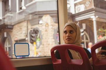 Hijab woman looking through window in the bus