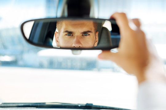 In the car. Close up of a rearview mirror with a smart skillful driver looking into it