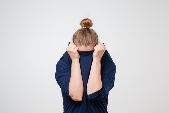 European woman hiding face under the clothes. She is oulling sweater on her head.