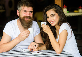 Enjoy moment with cup of coffee drink. Man with beard and attractive happy smiling girl hold hands drinking coffee. Couple in love drink black espresso coffee in cafe. Couple happy spend time in cafe