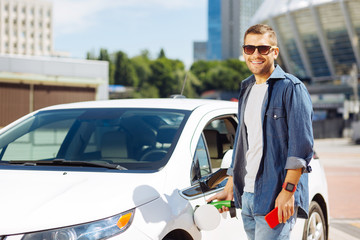 Positive mood. Cheerful handsome man smiling to you while fuelling his car