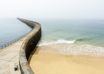 The Mole des Noires, the long breakwater of the walled city of Saint-Malo in Brittany, France, and the Mole beach by a sunny and misty weather. Wall mural