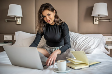 Happy beautiful young brunette woman relaxed smiling on bed on the computer and drinking coffee working