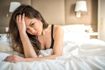 Happy beautiful sad thoughtful young brunette woman relaxed lying down on bed