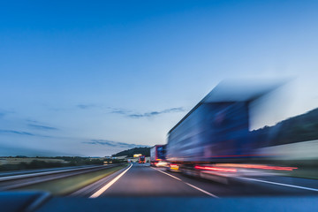 Background photograph of a highway. Truck on a motorway, motion blur, light trails. Evening or night shot of trucks doing logistics and transportation on a highway. Wall mural