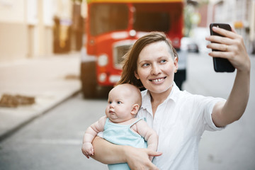 A young mother holds a baby in her arms, smiling and takes a photo on her smartphone while walking down the street against the backdrop of a red English bus. Maternity and blogging.