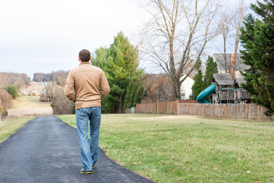 Back of young man walking on Sugarland Run Stream Valley Trail hike in Herndon, Northern Virginia, Fairfax county residential neighborhood in winter, spring, paved path road, houses