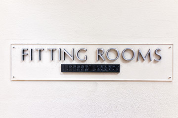 Fitting Room sign closeup in mall store shop retail clothing changing door entrance with nobody on wall, braille
