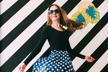 Cheerful young blonde woman dancing in a beautiful wall