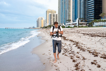 Sunny Isles Beach buildings during evening in Miami, Florida with sand, pier, shore coastline, people person photographer man walking with camera