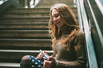 Smiling young woman holding vintage camera sitting on steps