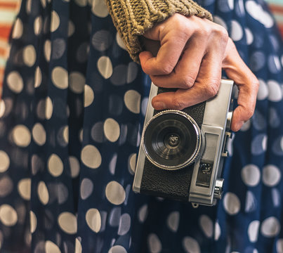 Crop woman holding a vintage camera