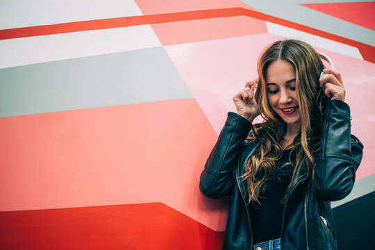 Happy young blonde woman in a colorful background listening to music