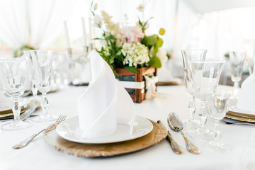 Table setting with fresh flowers on a white tablecloth in the restaurant