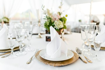 Table setting on a white tablecloth in the restaurant close-up