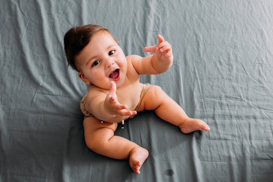 Top view of smiling baby sitting on the bed in the room wearing shorts