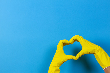 Hands in yellow rubber gloves making heart shape with fingers, on blue background