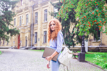 Red-haired girl student with folders and teaching materials in hands next to the university. Back to school concept. student life
