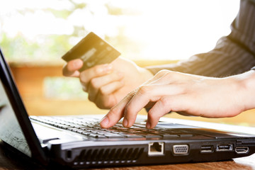 hand holding credit card and using laptop computer