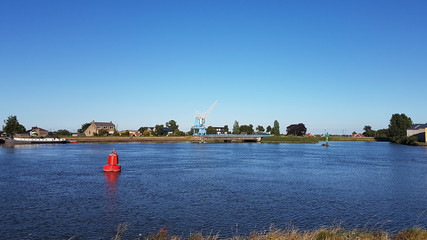 Red buoys on the water of river Hollandsche IJssel in the Netherlands with blue sky.